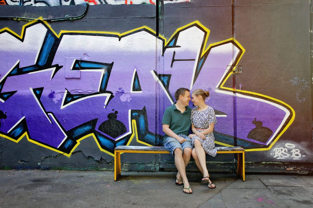 Couple sitting next to graffiti on London South Bank for Engagement Session