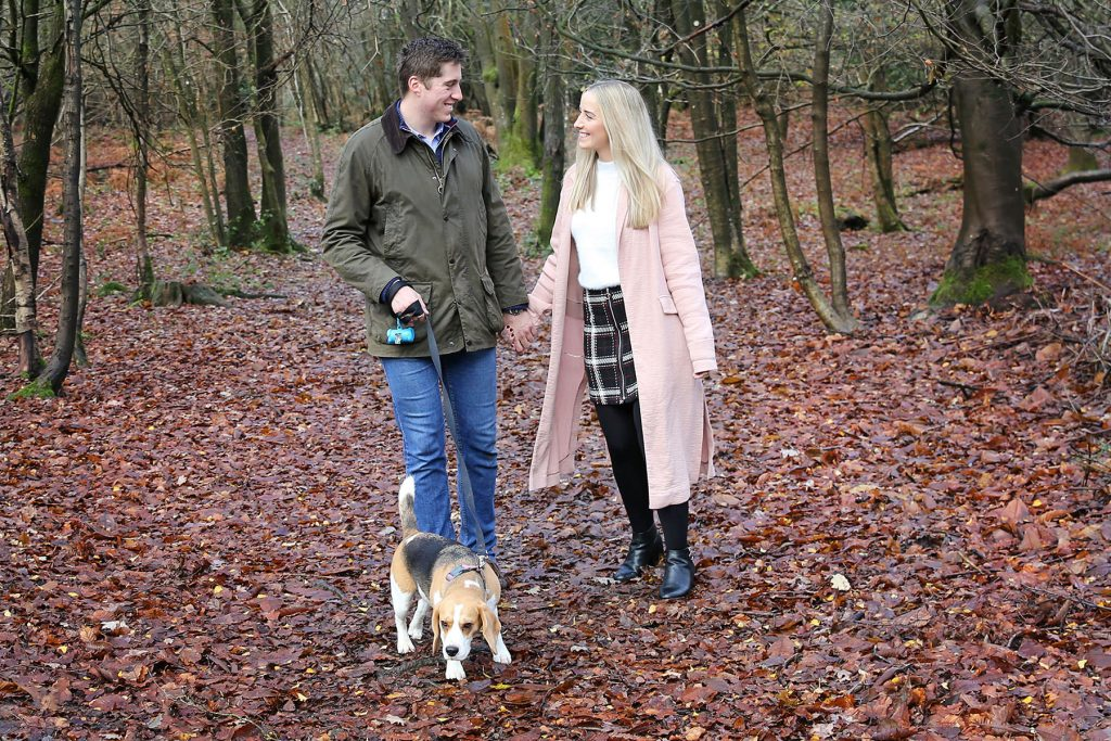 Engaged couple walking dog in Sussex woods for engagement photo session.