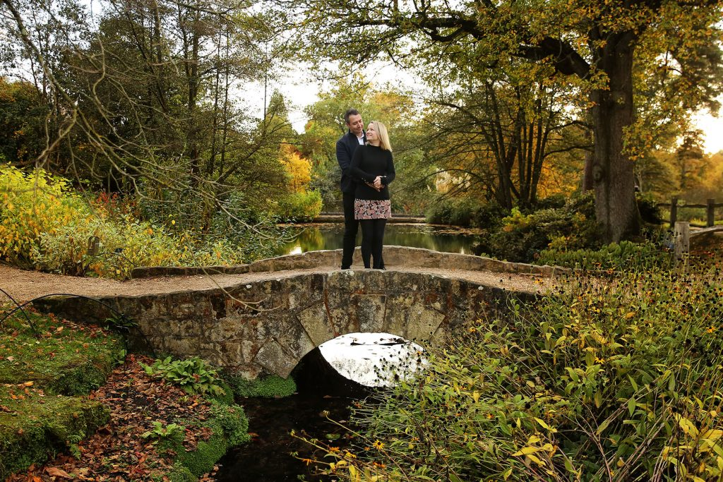 Engaged couple standing on stone bridge at Wakehurst Place for engagement photo