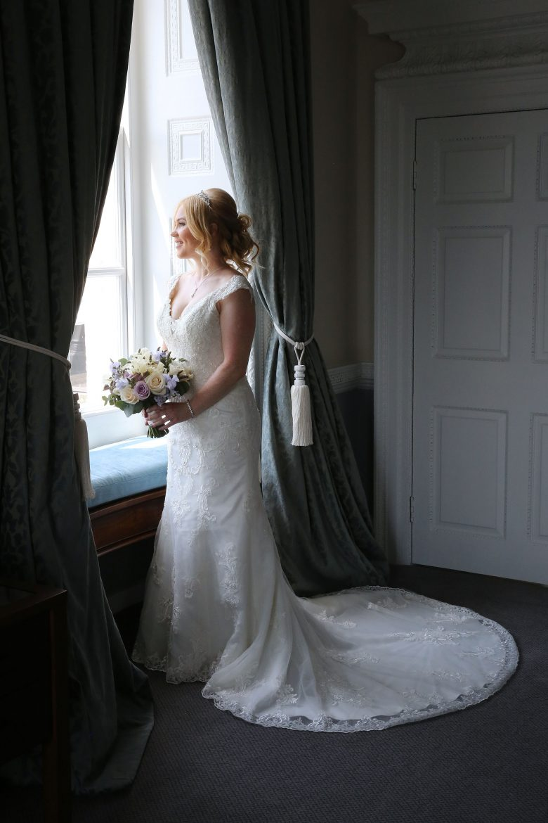 bride looking out of the window holding her flowers at Buxted park Hotel