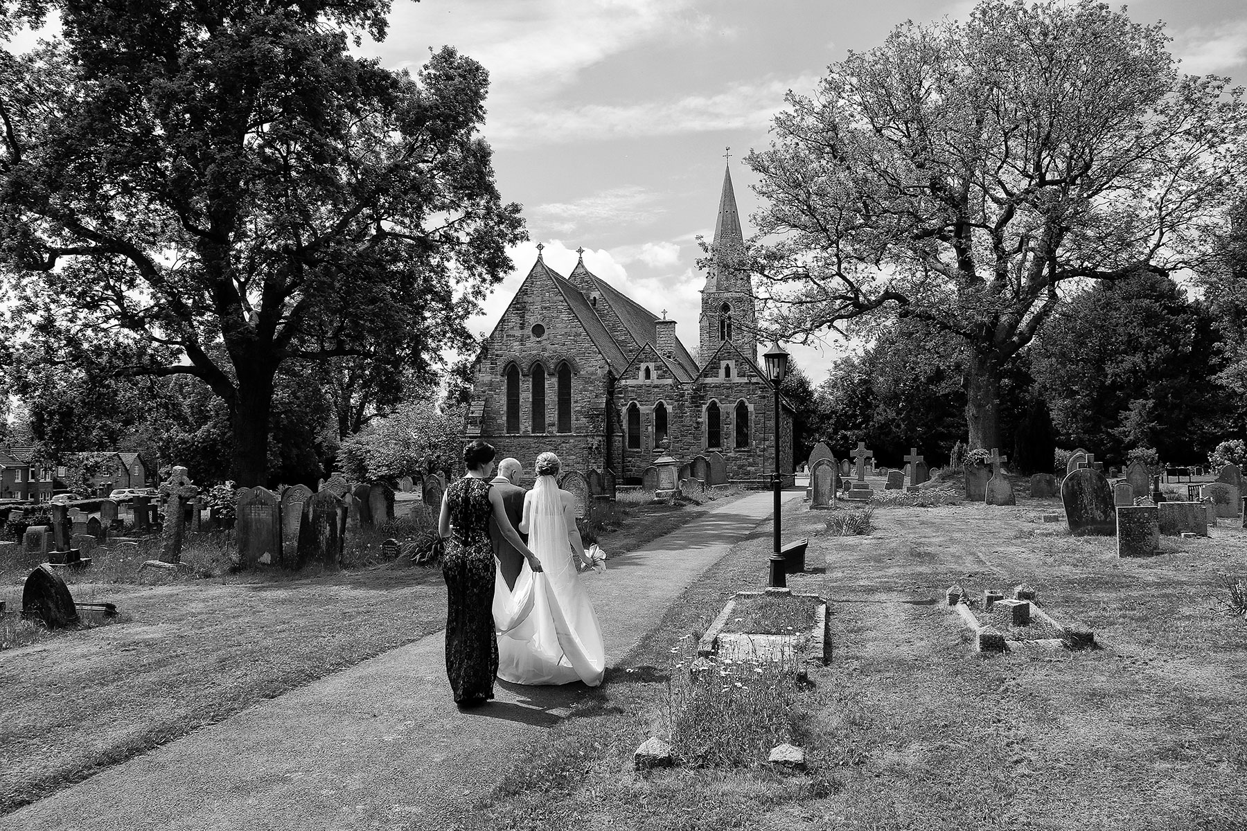 bride walking towards church with father and bridesmaid carrying the dress, Sussex Wedding Photographers