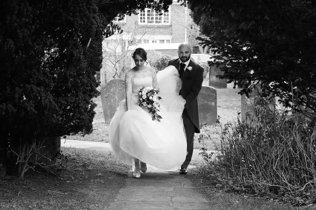 bride walking up path with dad carrying the dress, Sussex Wedding Photographers