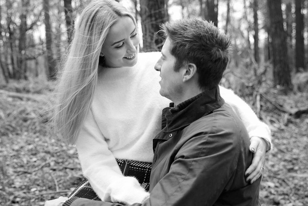 Girl sitting on boys lap for engagement images