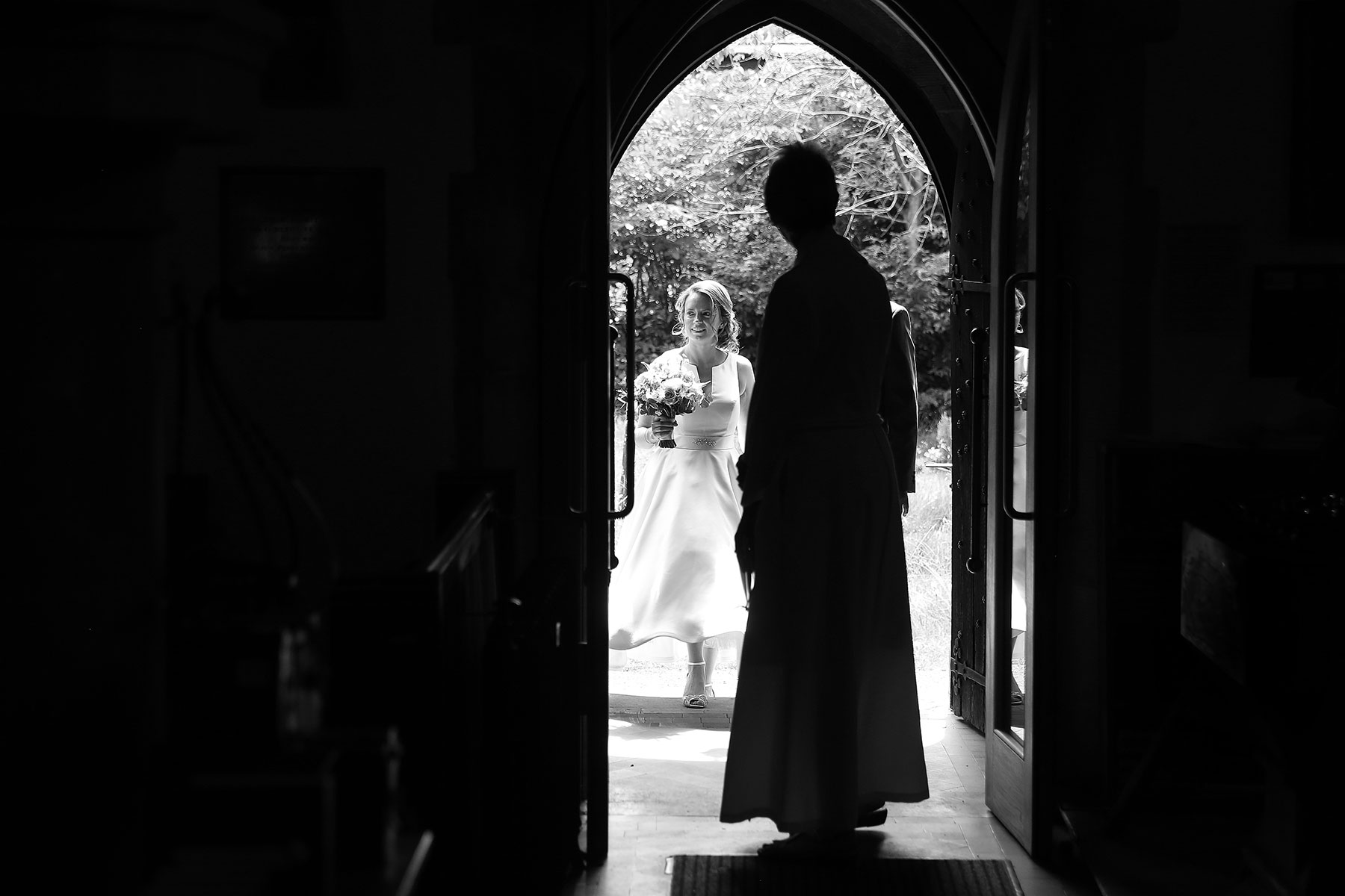 bride arriving at crawly down church with vicar looking on, Sussex Wedding Photographers