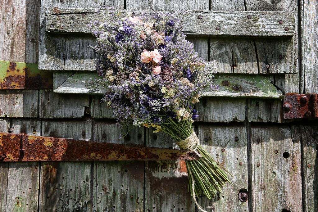 flowers on old door handle at old green barn in rusper, Sussex Wedding Photographers