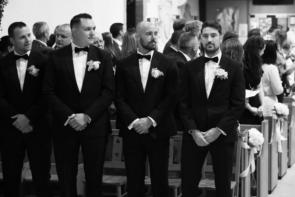 groomsman looking at groom at worth church just before the arrival of the bride, Sussex Wedding Photographers