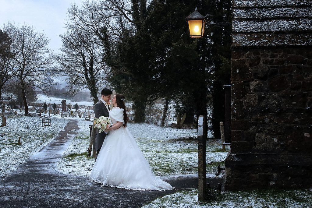 bride and groom standing outside brasted church in the snow, Sussex Wedding Photographers