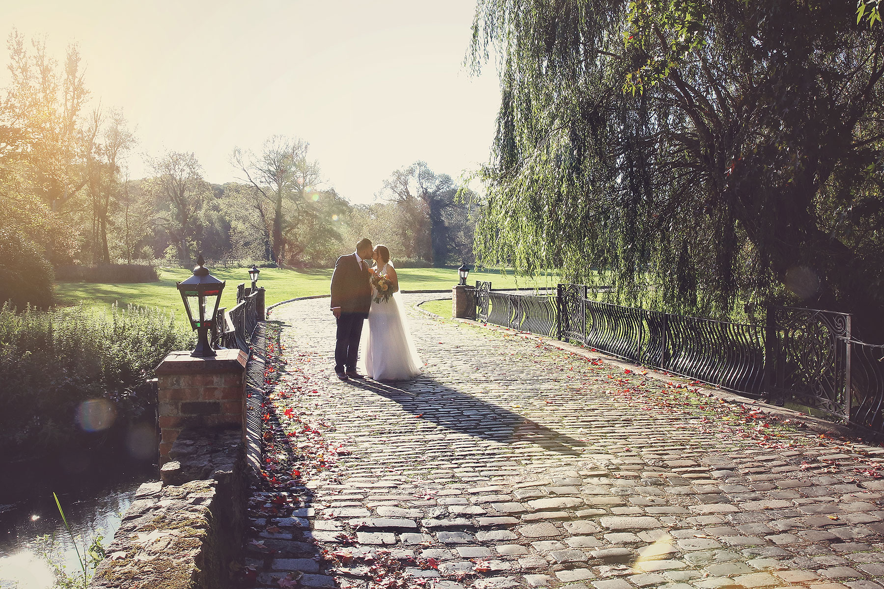 bride and groom kissing on the bridge at The Mill at Elstead