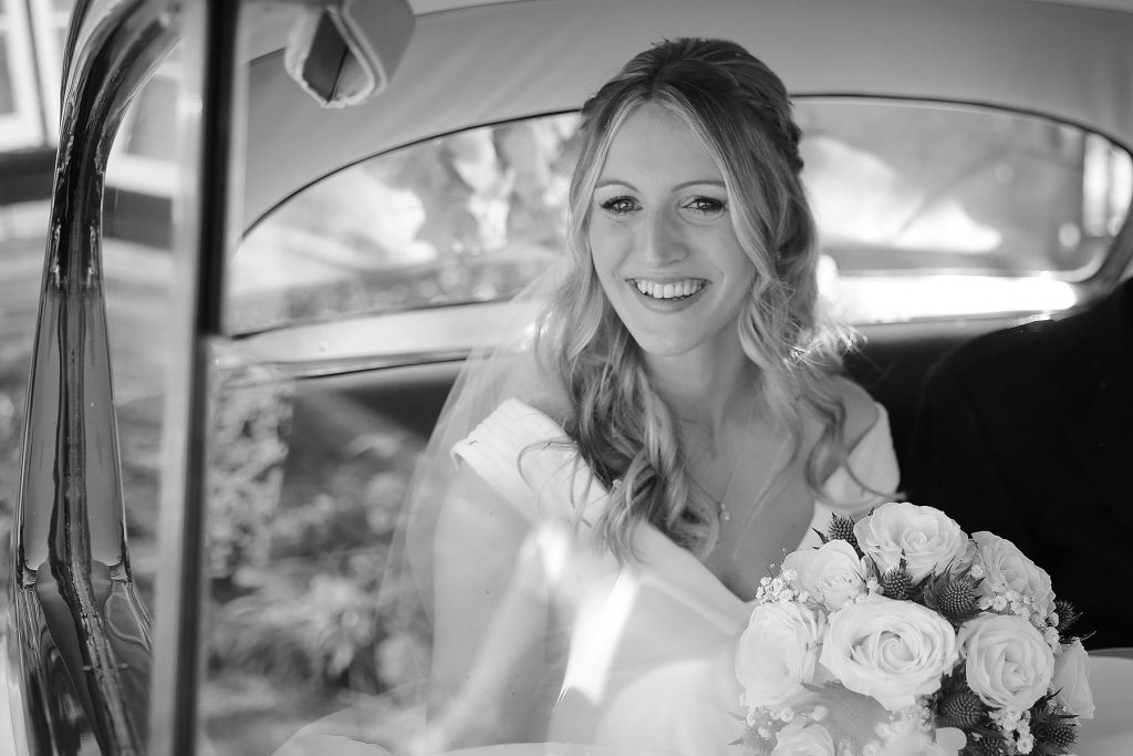 bride looking out of car window at worth church, Sussex Wedding Photographers