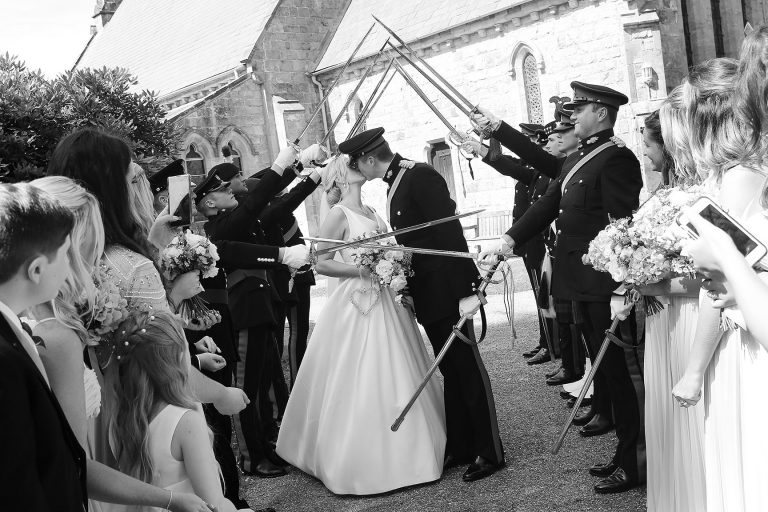 Bride and Groom walking through military guard of honour at All Saints Church, Crawley Down